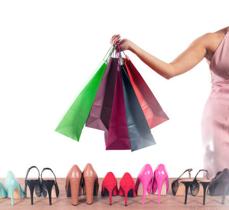 Girl full of bags does shopping in a shoes store