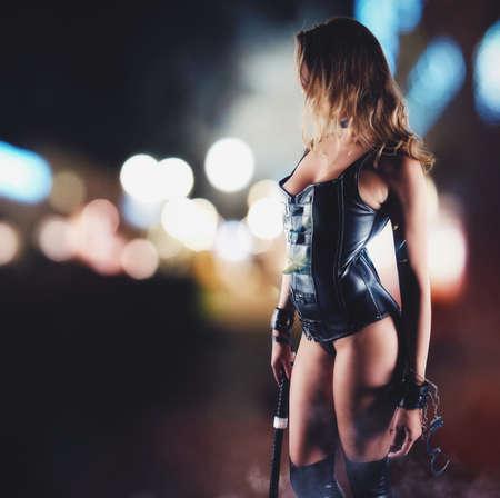 鞭を持つ女性の官能的な挑発