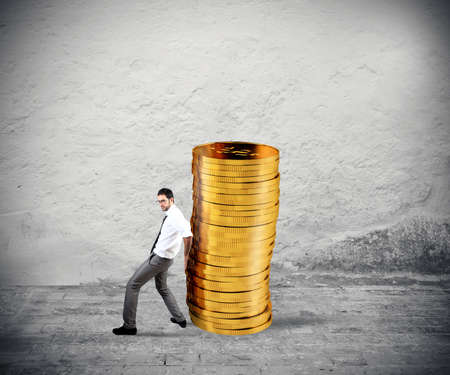 Businessman moves a pile of coins. concept of difficulty to saving money