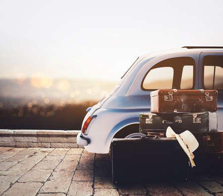 Coche en la carretera listo para las vacaciones de verano durante la puesta de sol con equipaje Foto de archivo