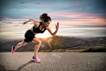 Athletic woman runs on the street during sunset Standard-Bild - 105706536