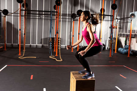 Athletic girl does box jump exercises at the gym Standard-Bild - 105715760