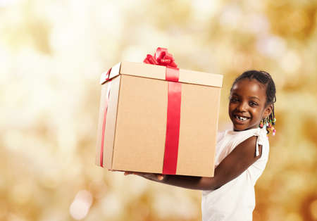 Happy little girl with a Christmas gift Standard-Bild - 107617870