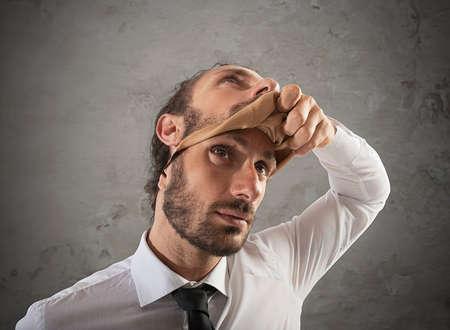 Hombre de negocios que se quita la máscara. Concepto de falsedad
