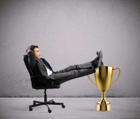 Winner businessman relaxing over a golden cup