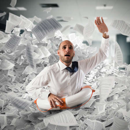 Businessman with lifebuoy sinks between worksheets in office Standard-Bild