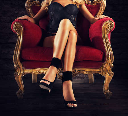 Sensual woman on a red velvet armchair Standard-Bild
