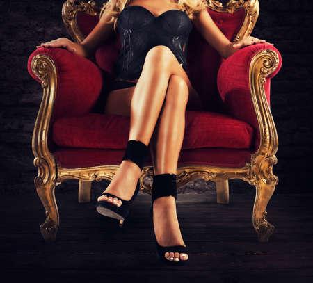 Sensual woman on a red velvet armchair Stockfoto