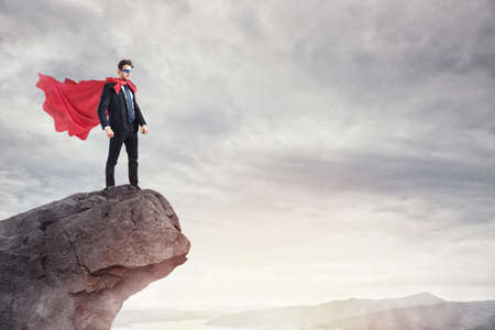 Businessman as a super hero on the peak of a mountain Stock Photo