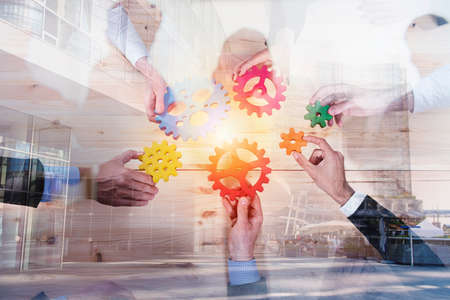 Business team connect pieces of gears. Teamwork, partnership and integration concept. double exposure