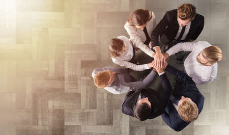 Ludzie biznesu, składając ręce. Koncepcja integracji, pracy zespołowej i partnerstwa