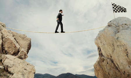 Business concept of businessman who overcome the problems reaching the flag on a rope Stok Fotoğraf - 109512808