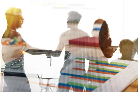 Silhouette of young workers shaking hands in the office. concept of teamwork and partnership. double exposure