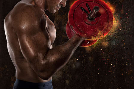 Athletic muscular man training biceps at the gym with fire effect