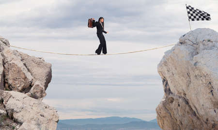 Business concept of businesswoman who overcome the problems reaching the flag on a rope