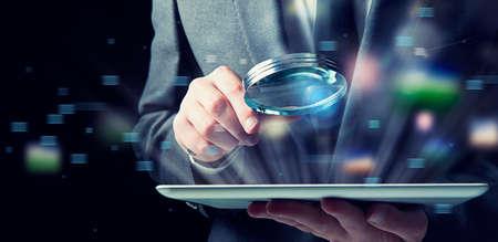 Zakenman onderzoekt een tablet met een vergrootglas. Concept van internetbeveiliging