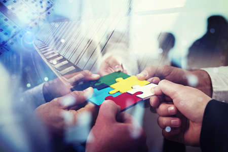 Ludzie biznesu dołączają do puzzli w biurze. Pojęcie pracy zespołowej i partnerstwa. podwójna ekspozycja z efektami świetlnymi
