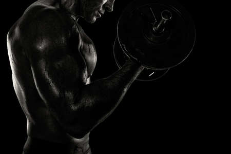 Athletic man training biceps at the gym. black and white effect Stock Photo