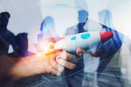Businessman launches his startup company. Hand holding a wooden rocket. double exposure with light effects Stock Photo