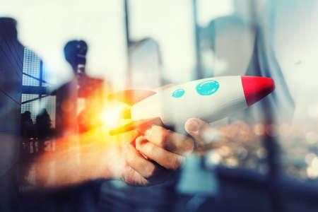 Zakenman lanceert zijn startbedrijf. Hand met een houten raket. dubbele belichting met lichteffecten