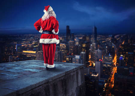 Santa Claus looks down on the city waiting to deliver the presents Фото со стока