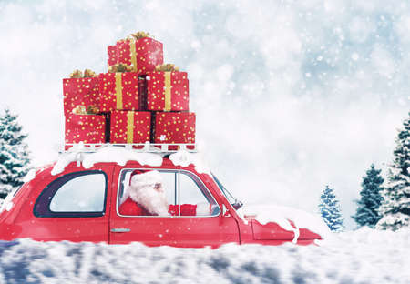 Santa Claus on a red car full of Christmas present with winter background drives to deliver Reklamní fotografie