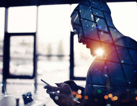 Businessman works with his smartphone in office. double exposure