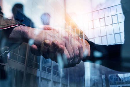 Handshaking business person in office. concept of teamwork and partnership. double exposure Reklamní fotografie
