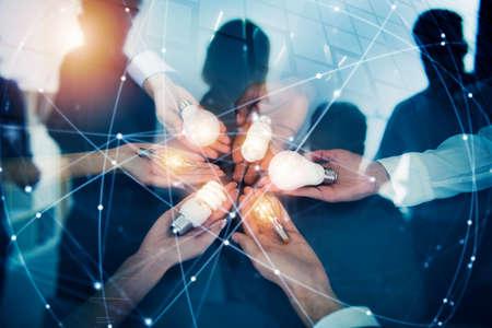 Concept de travail d'équipe et de remue-méninges avec des hommes d'affaires qui partagent une idée avec une lampe. Concept de démarrage. Double exposition Banque d'images