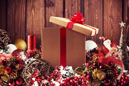 Christmas gift box presented in the middle of Christmas decorations on wooden planks