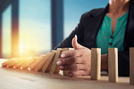 Businesswoman stops a chain fall like domino game. Concept of preventing crisis and failure in business Stock Photo