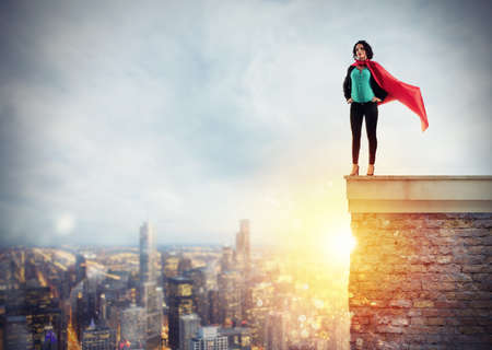 Successful businesswoman acts like a super hero above the roof of a building. Concept of determination and success
