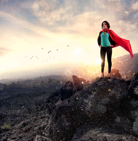 Successful businesswoman acts like a super hero on a mountain.