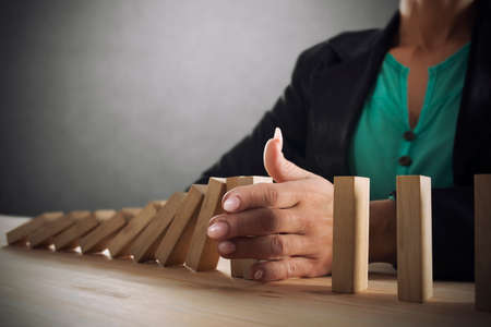 Businesswoman stops a chain fall like domino game. Stock Photo