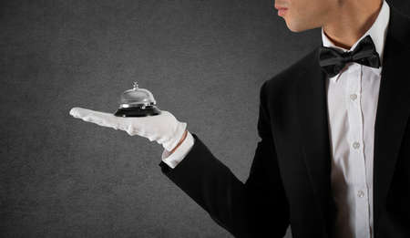 Waiter with bell in hand. Concept of first class service in your business 스톡 콘텐츠 - 113929391