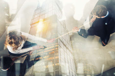 Rival business man and woman compete for the command by pulling the rope. Double exposure effect Stock Photo