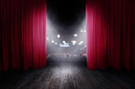 Las cortinas rojas se abren para el espectáculo de teatro.