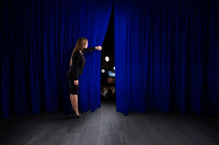 Woman open blue curtains of the theater stage