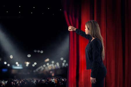 Frau öffnet rote Vorhänge der Theaterbühne