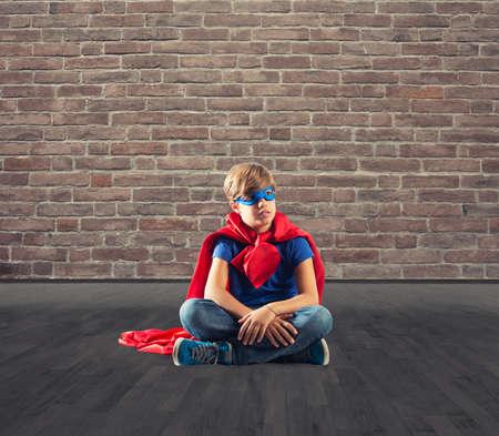 Superhero kid sitting on a wall that dreams Stock Photo