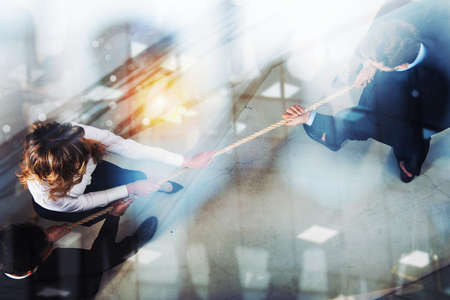 Rival business man and woman compete for the command by pulling the rope. Double exposure effect Stock Photo - 115371916
