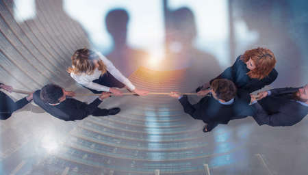 Rival business man and woman compete for the command by pulling the rope. double exposure