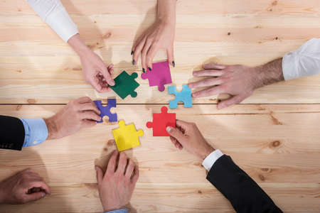 Business people join puzzle pieces in office. Concept of teamwork and partnership