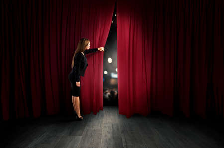 Woman open red curtains of the theater stage Imagens - 115372521
