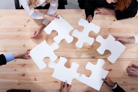 Business people work together to build a puzzle. Concept of teamwork, partnership, integration and startup