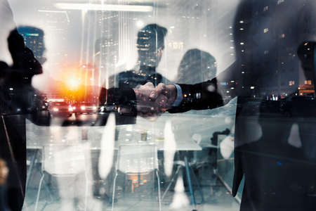 Handshaking business person in office. concept of teamwork and partnership. double exposure Stock Photo