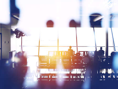 Double exposure with silhouettes of passengers in the airport waiting for boarding
