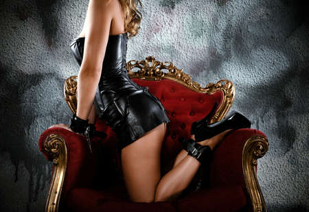 Sensual provocation of a sexy bdsm woman on an armchair