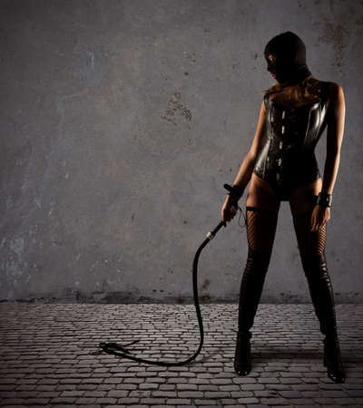Sensual provocation of a sexy bdsm woman with whip