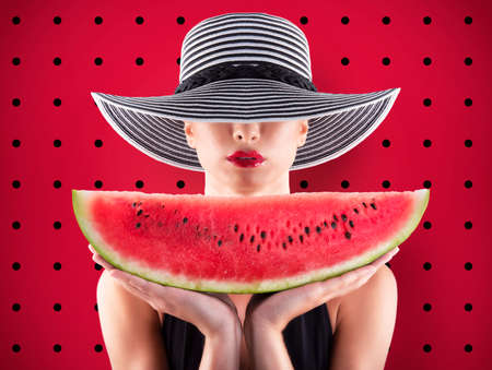 Girl in swimsuit with watermelon in hand and red background Stock Photo